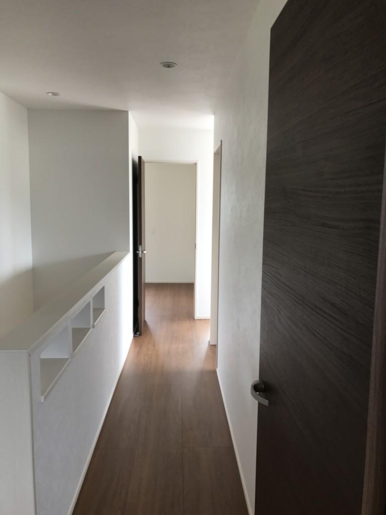 シンプルでモダンな感じの2F廊下、手すりのスリットにはお気に入り小物で飾り付け